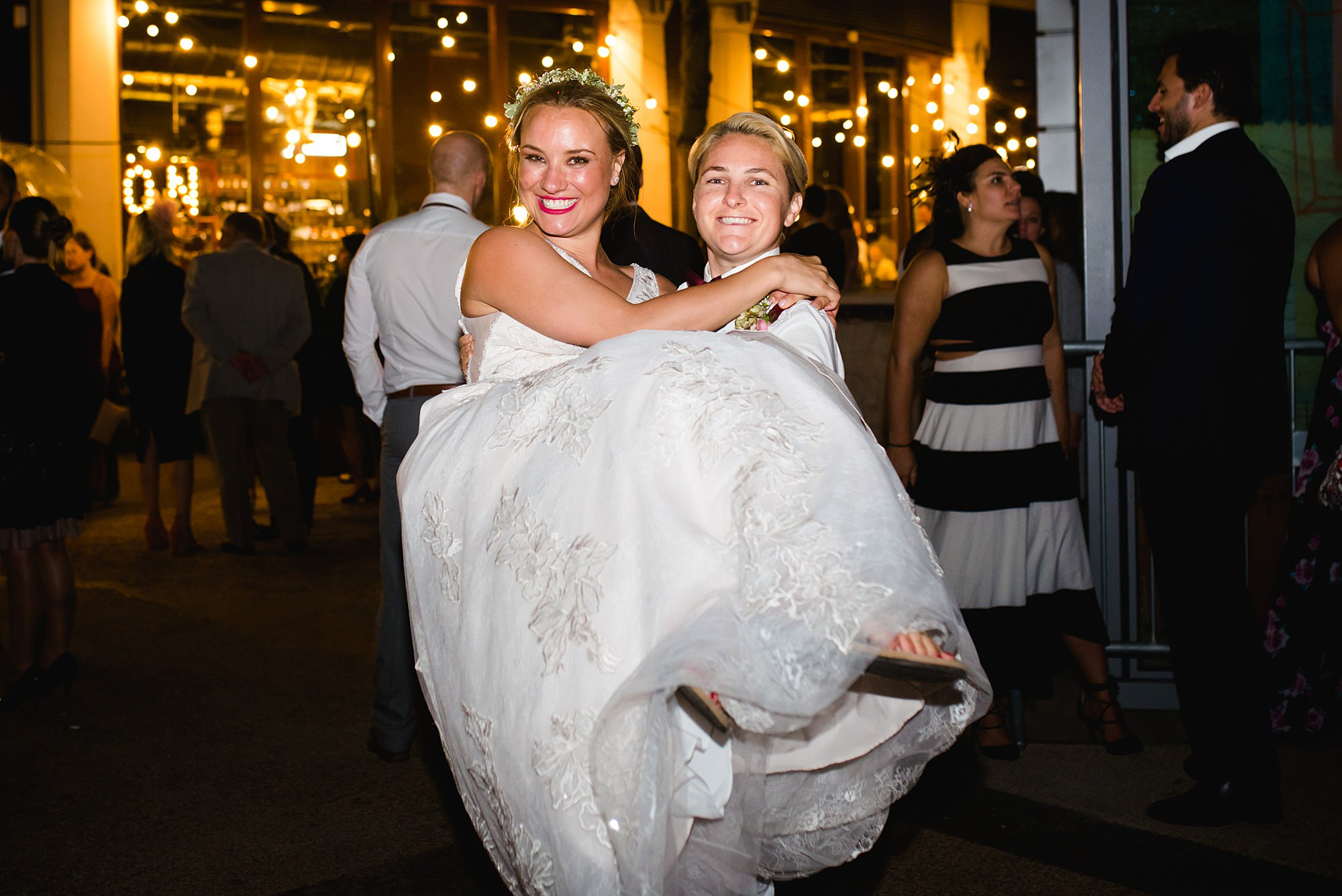 fun portrait of bridesmaid carrying bride at the union pub wedding