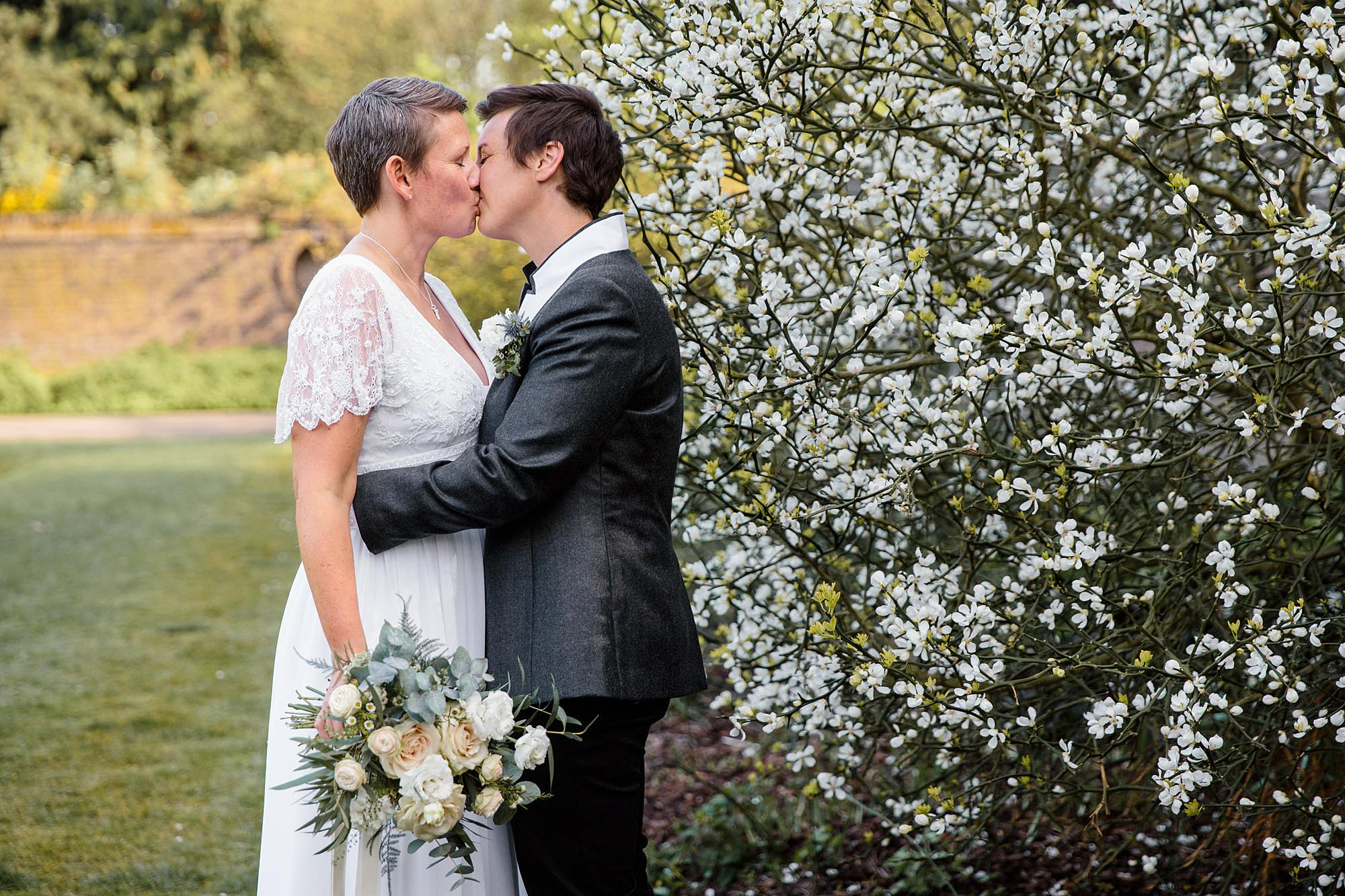 Twickenham wedding photography brides kiss by blossom at work house gardens