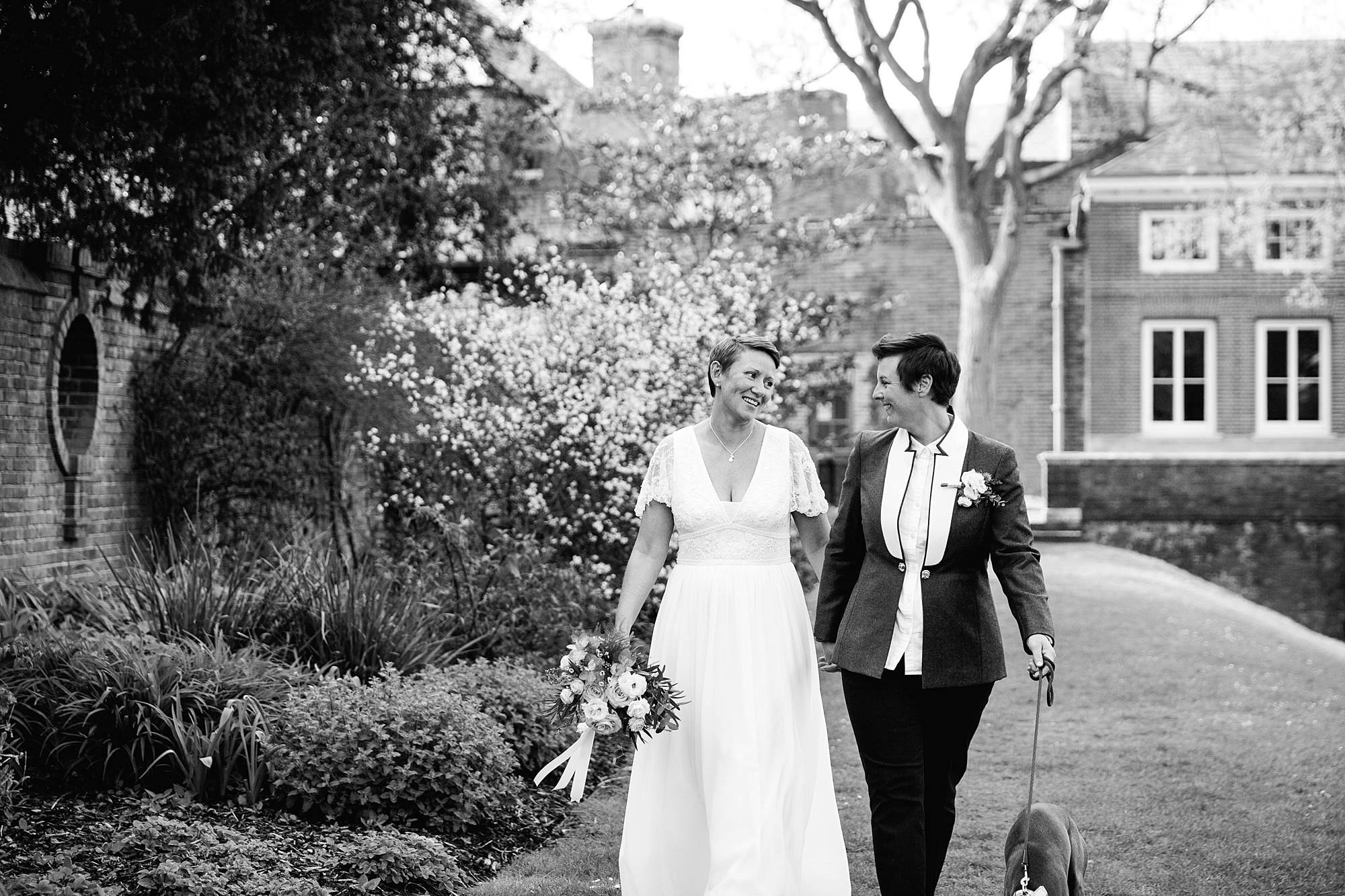 Twickenham wedding photography brides laugh together as they walk through york house gardens