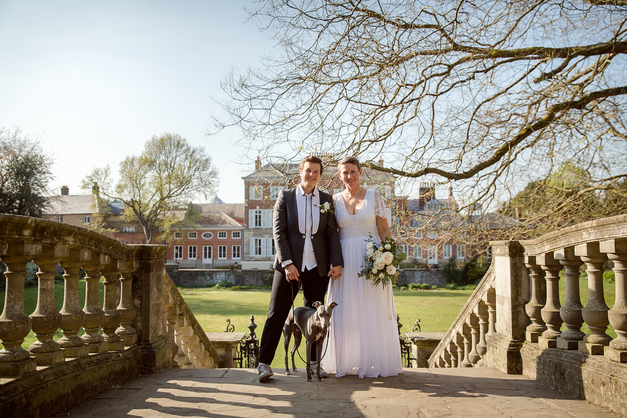 Twickenham wedding photography brides stand with their whippet dog on bridge outside york house