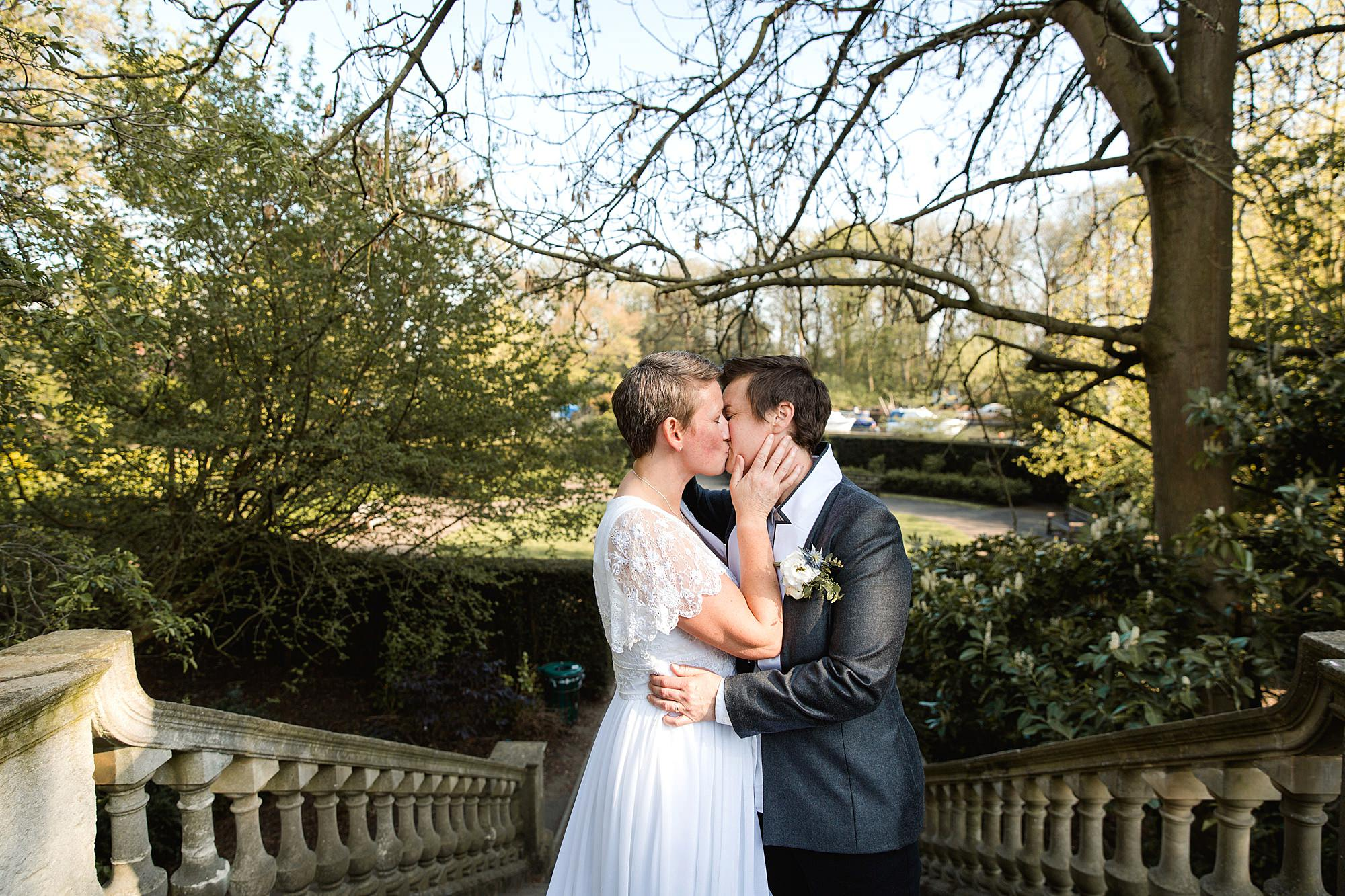 Twickenham wedding photography brides kiss on top of bridge at york house