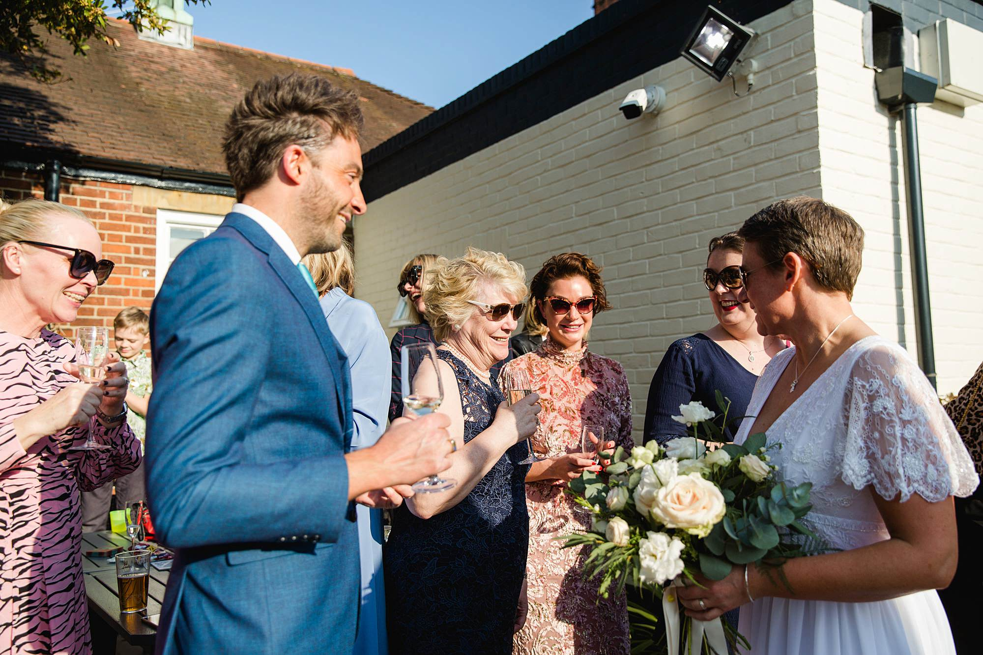 wedding guests greet brides at works head pub
