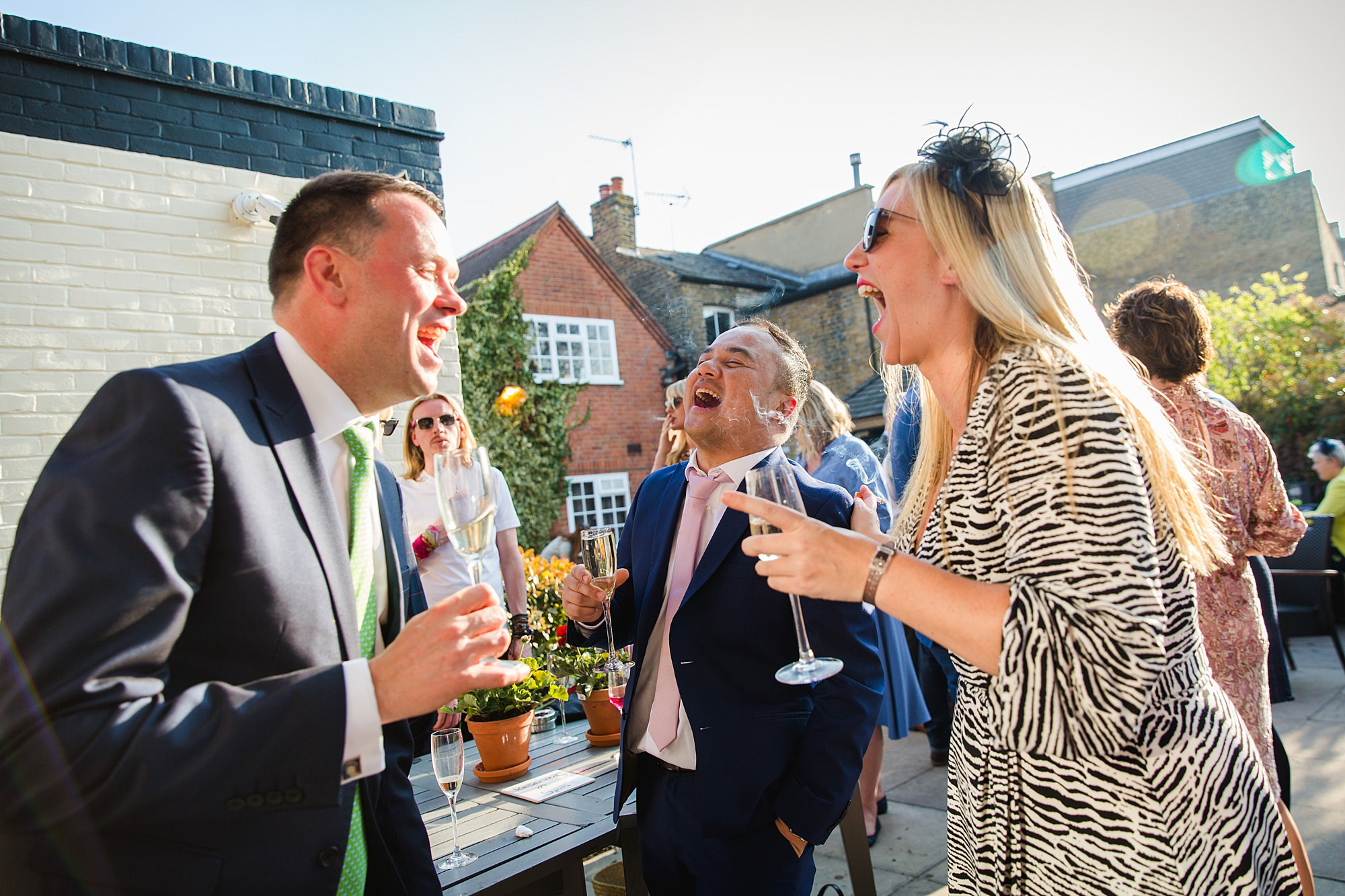 wedding guests laughing together at twickenham pub wedding