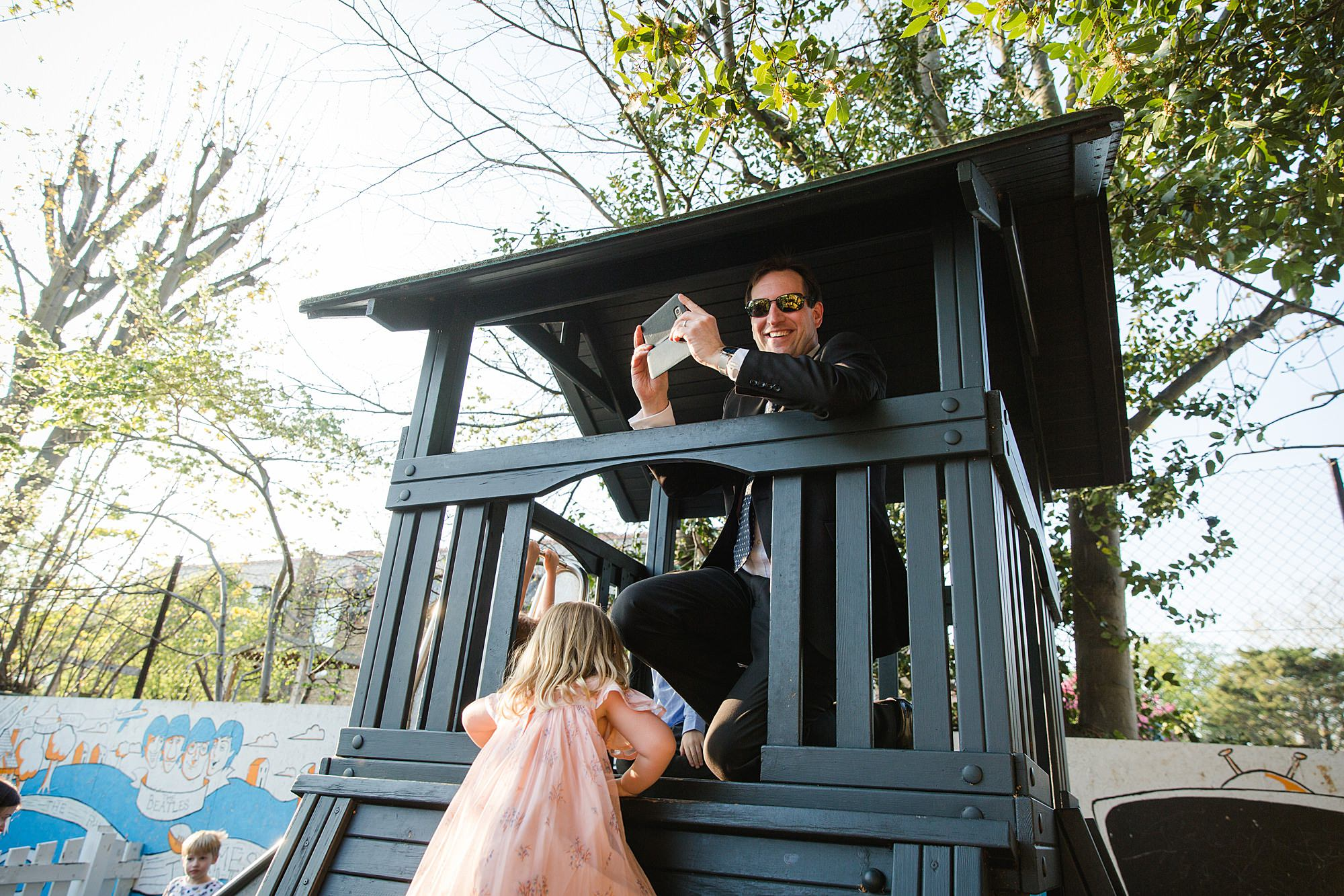 fun portrait of wedding guest on children's slide house