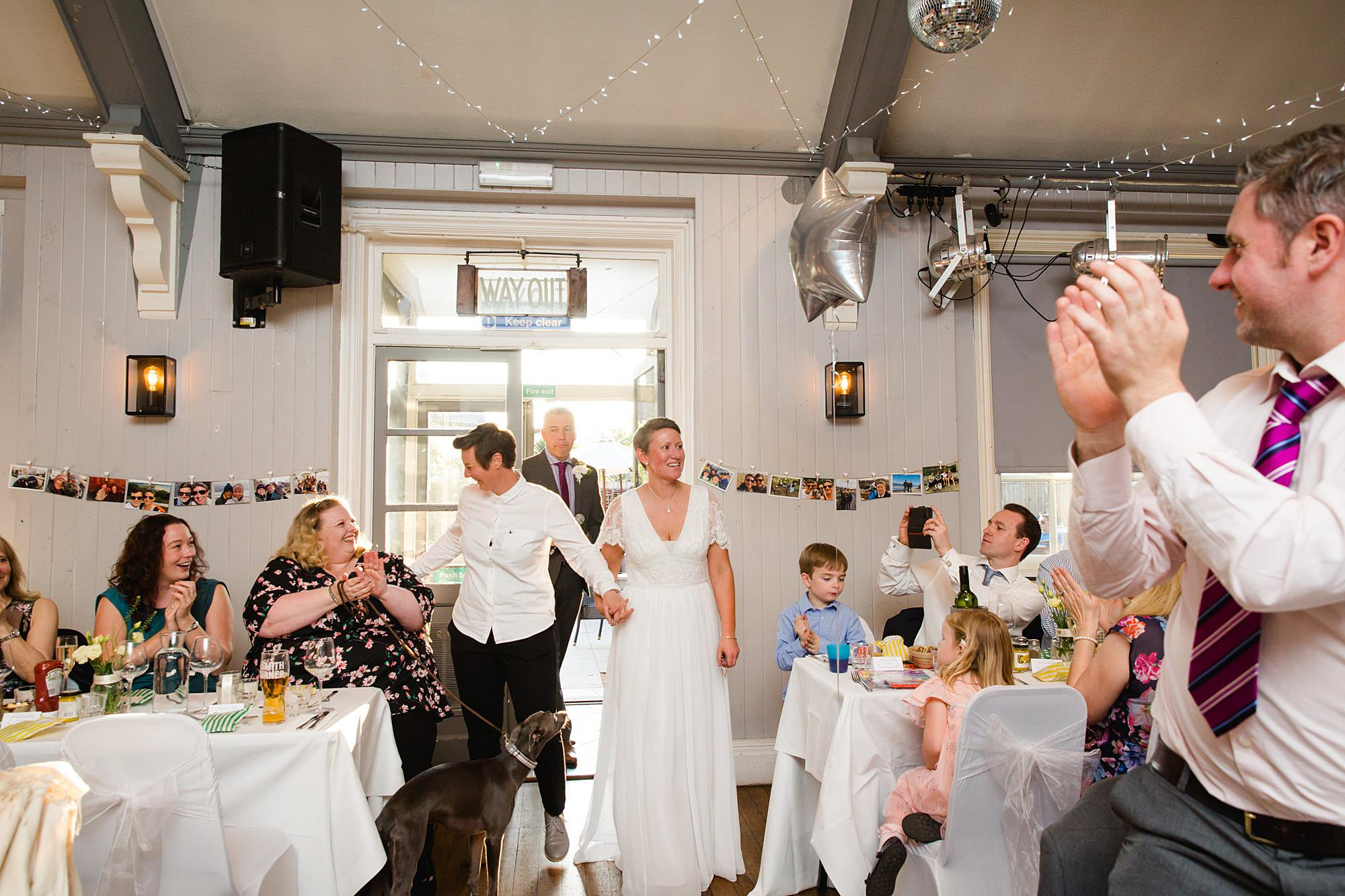 Twickenham wedding photography brides enter to guest cheers at turks head pub