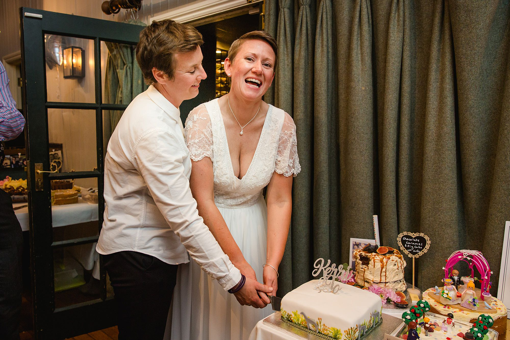 Twickenham wedding photography brides laugh and cut cake