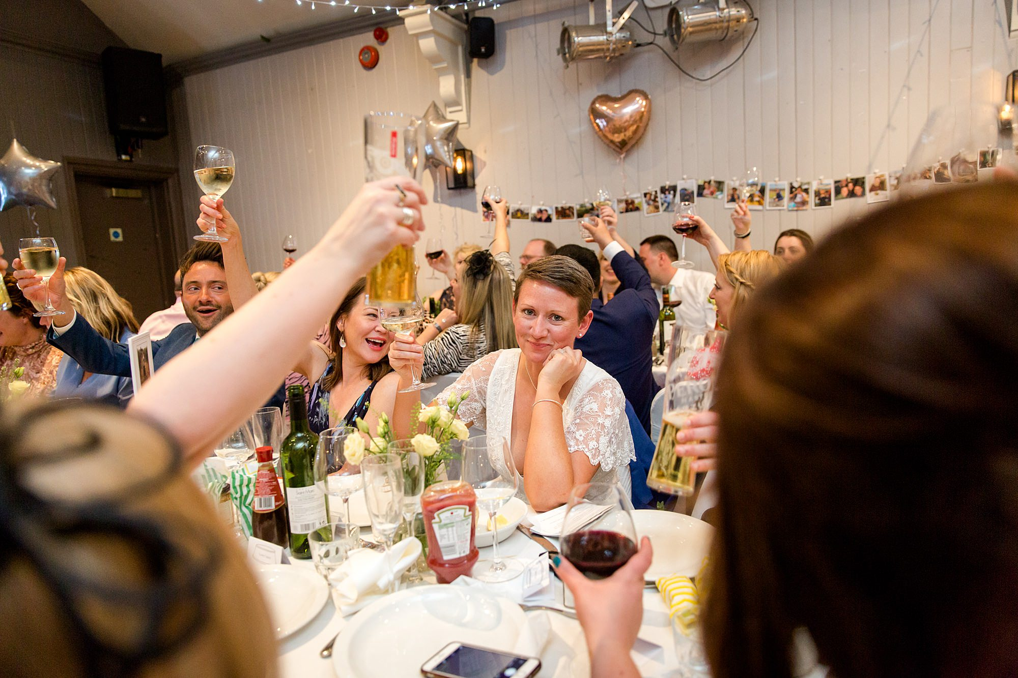 brides raise a toast during speeches at turks head pub wedding