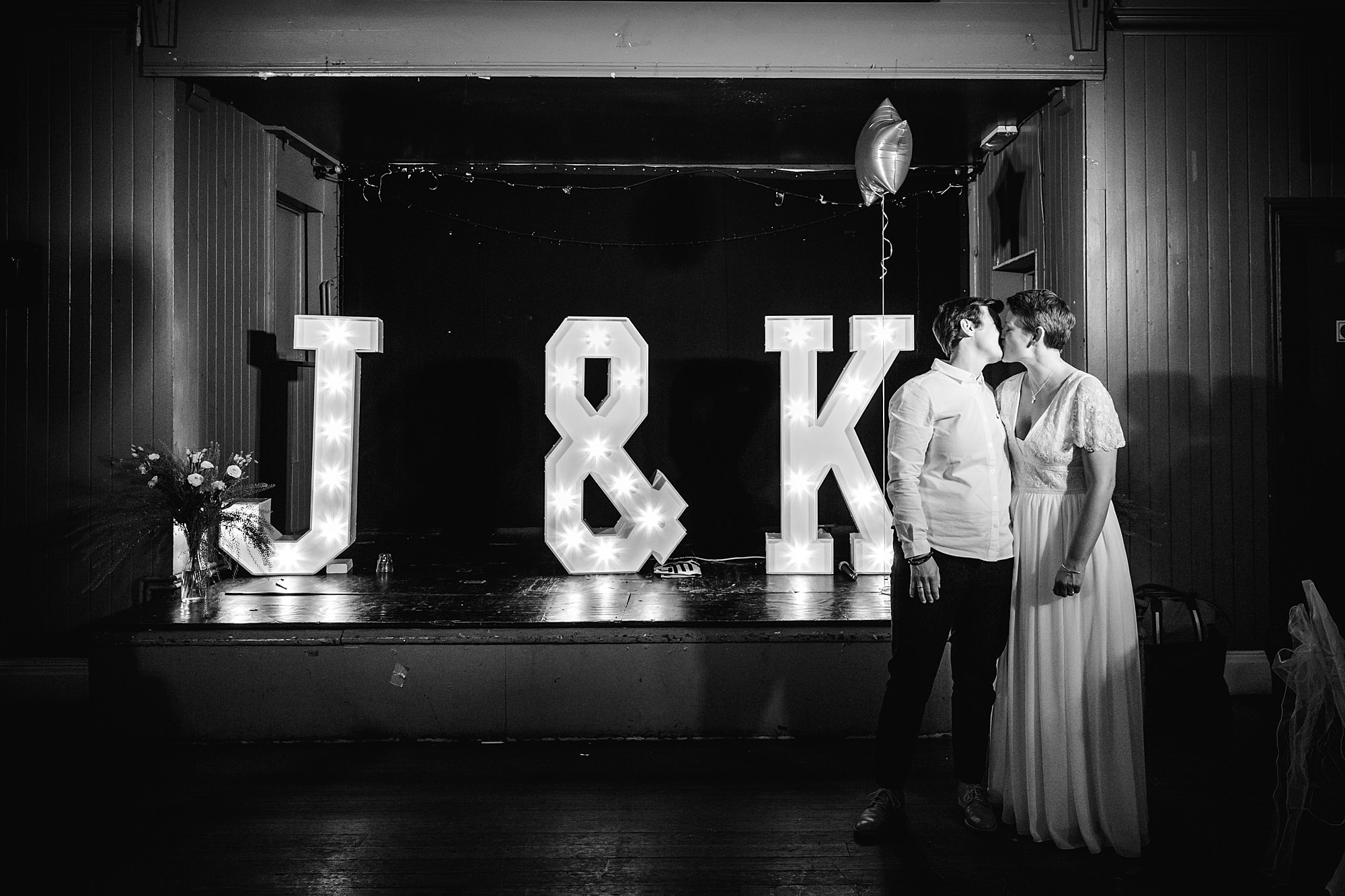 Twickenham wedding photography bride and groom kiss in from of light up initials at turks head pub