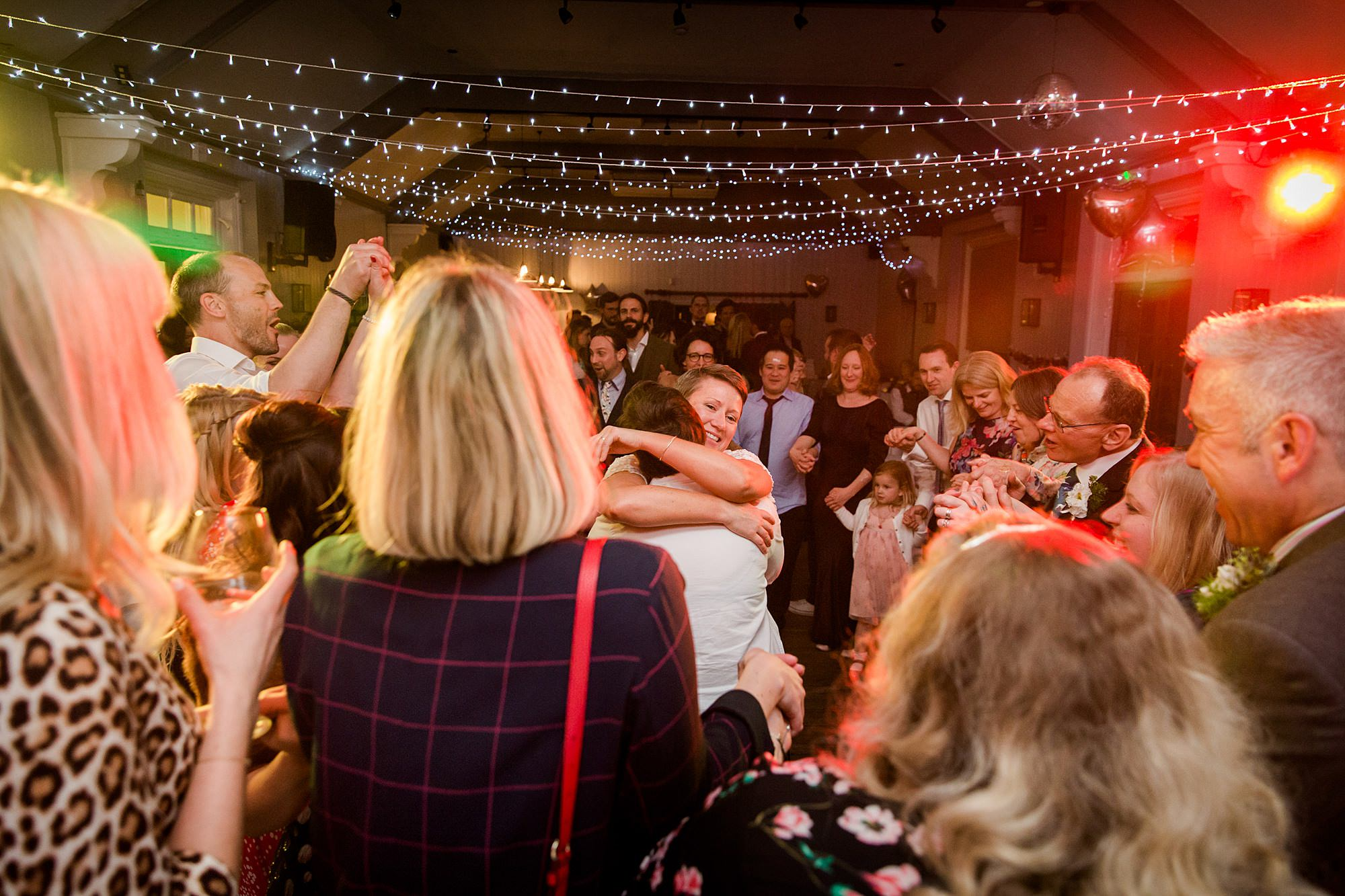 Twickenham wedding photography brides hug and dance together at turks head pub