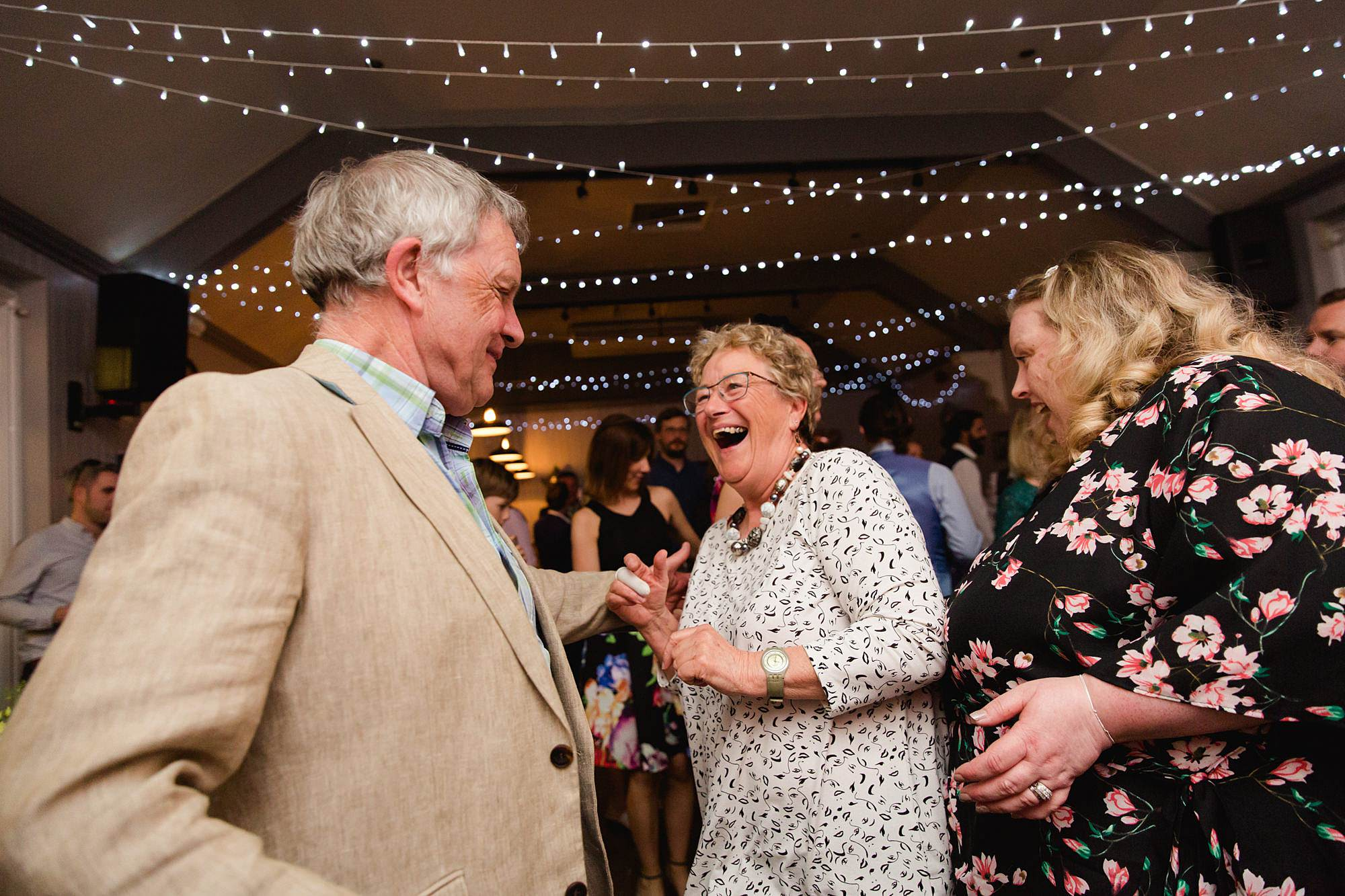 Twickenham wedding photography guests laugh and dance together