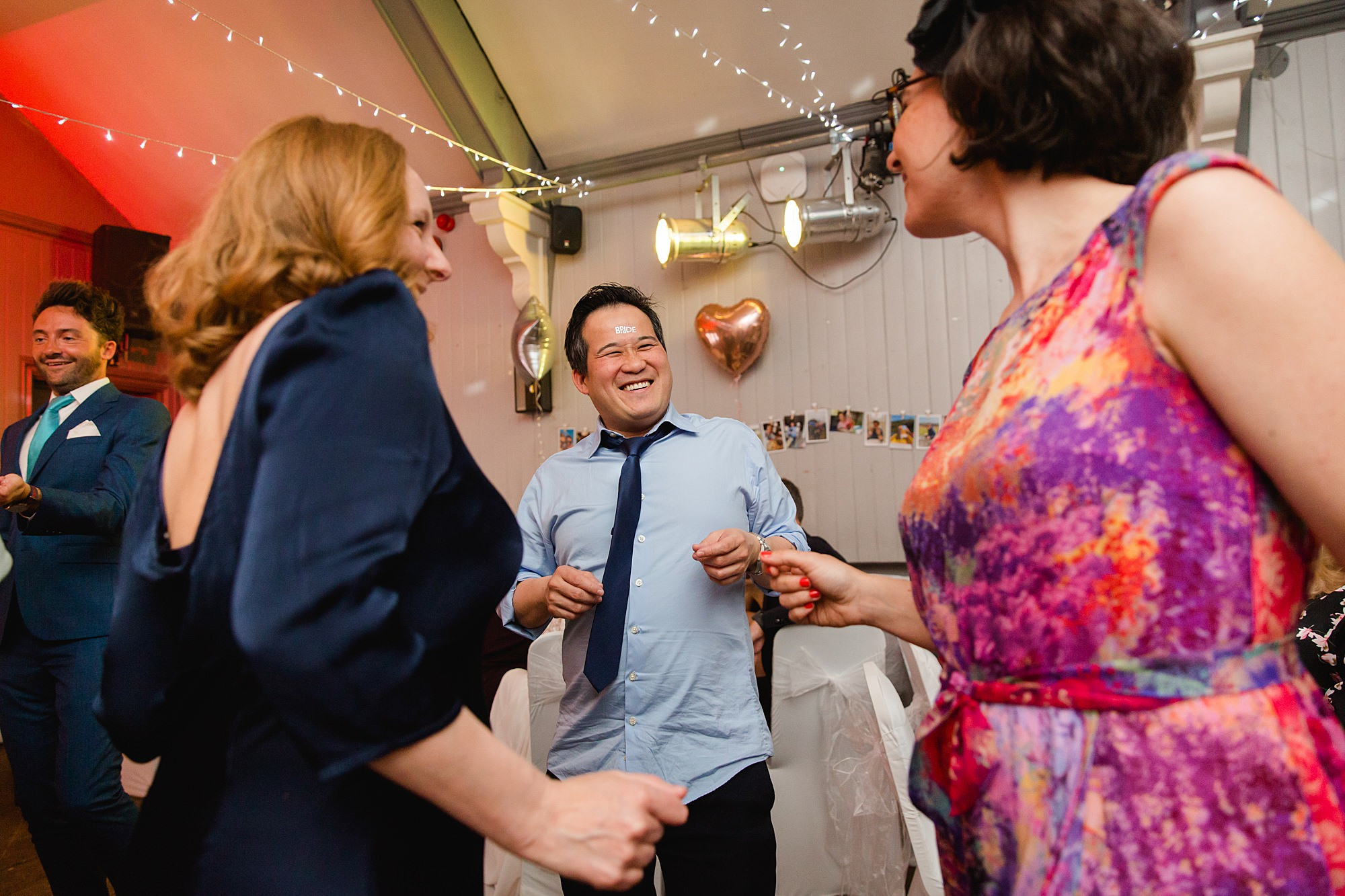 guests laugh at dance together at twickenham pub wedding