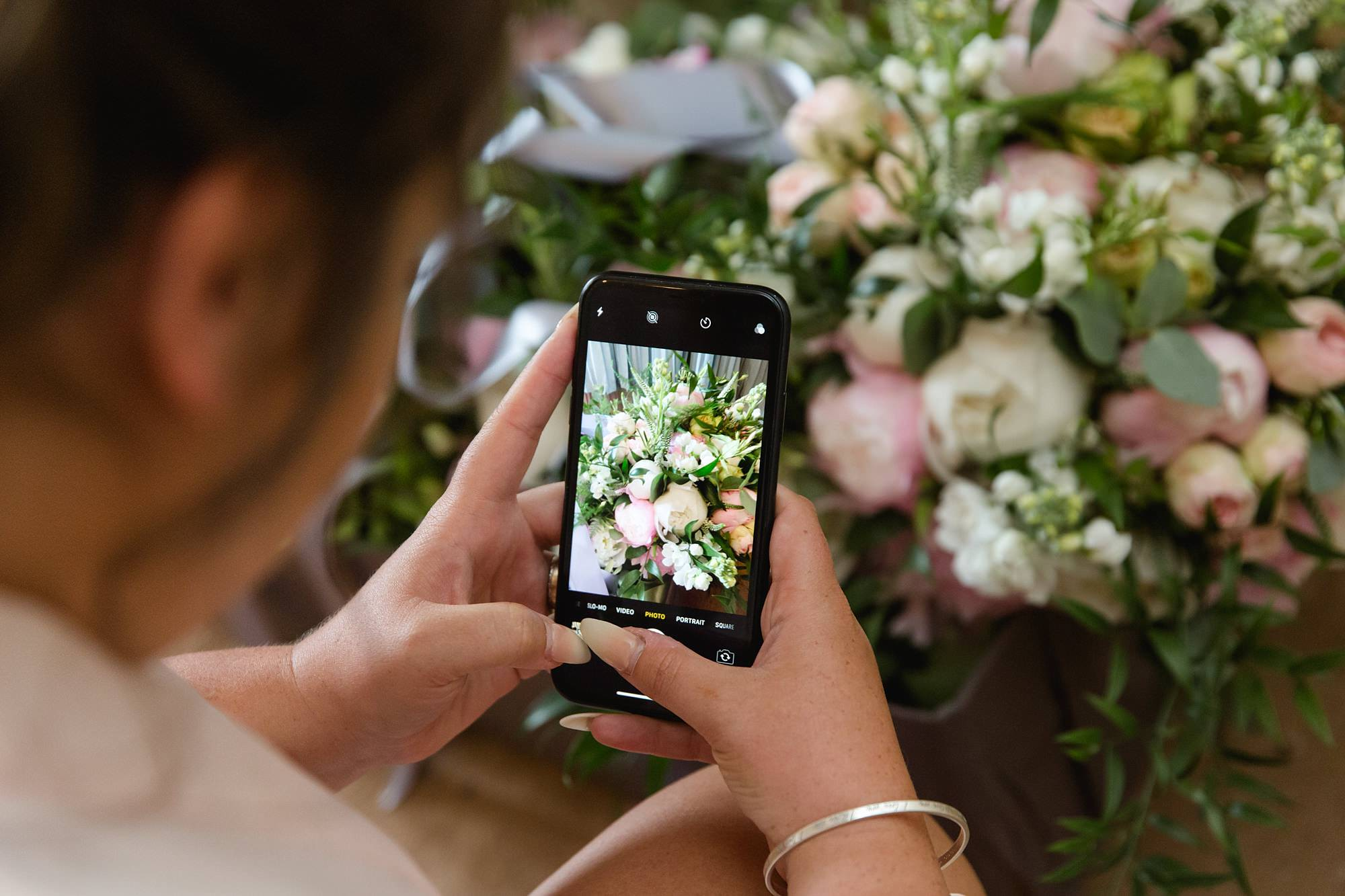 bridesmaid takes picture of wedding bouquet