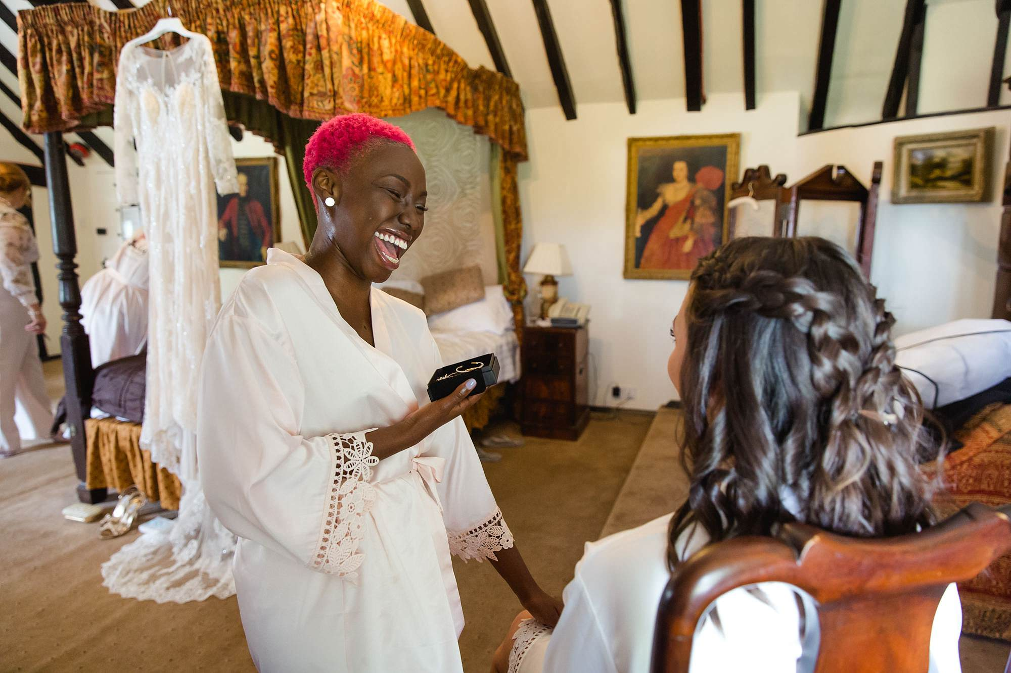 bridesmaid laughing with bride while getting ready for humanist wedding