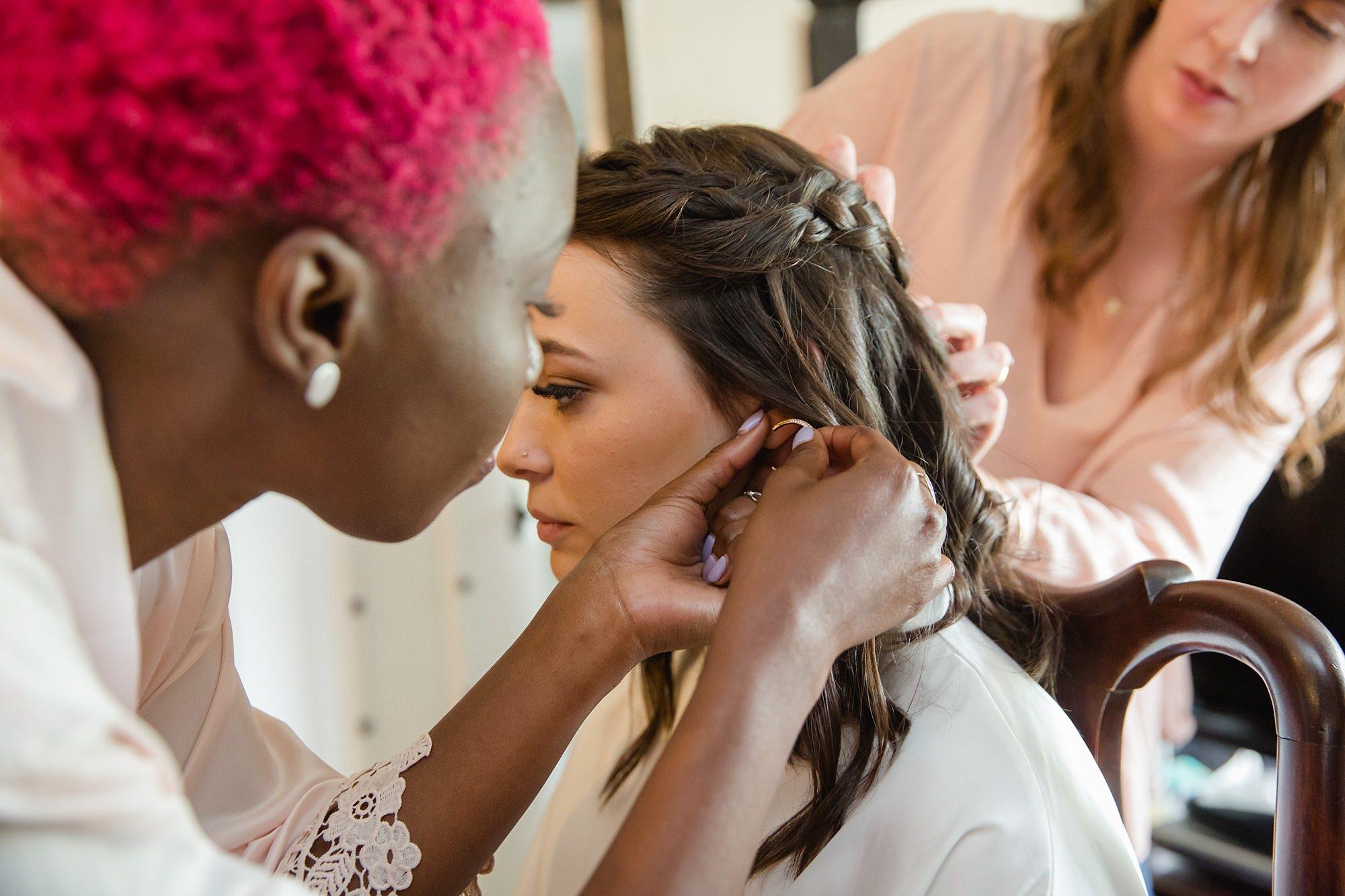 bridesmaid helps bride with earrings ahead of old greens barn wedding