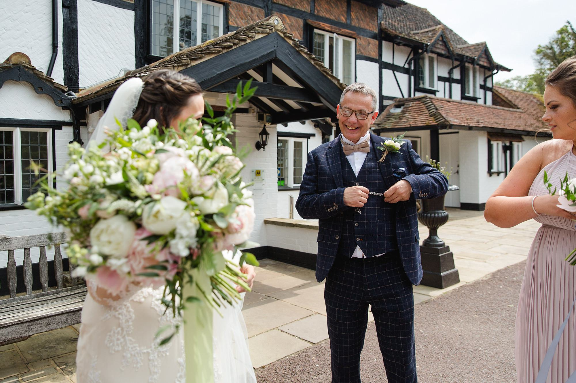 bride gives her father a pocket watch ahead of old greens barn wedding