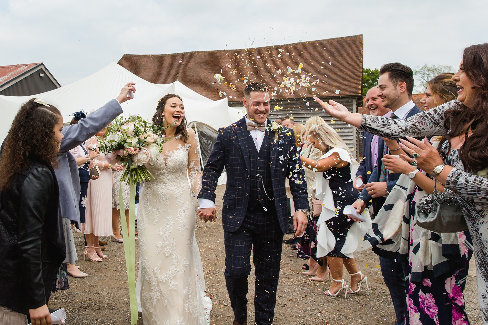 guests thrown confetti over bride and groom at humanist wedding old greens barn