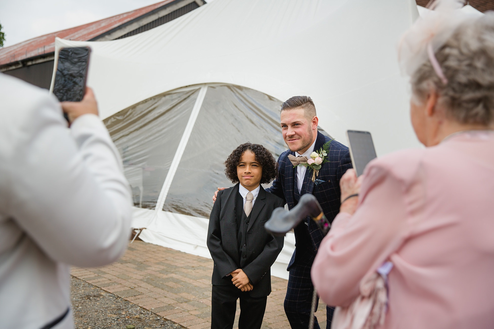 groom poses with little wedding guest at old greens barn wedding