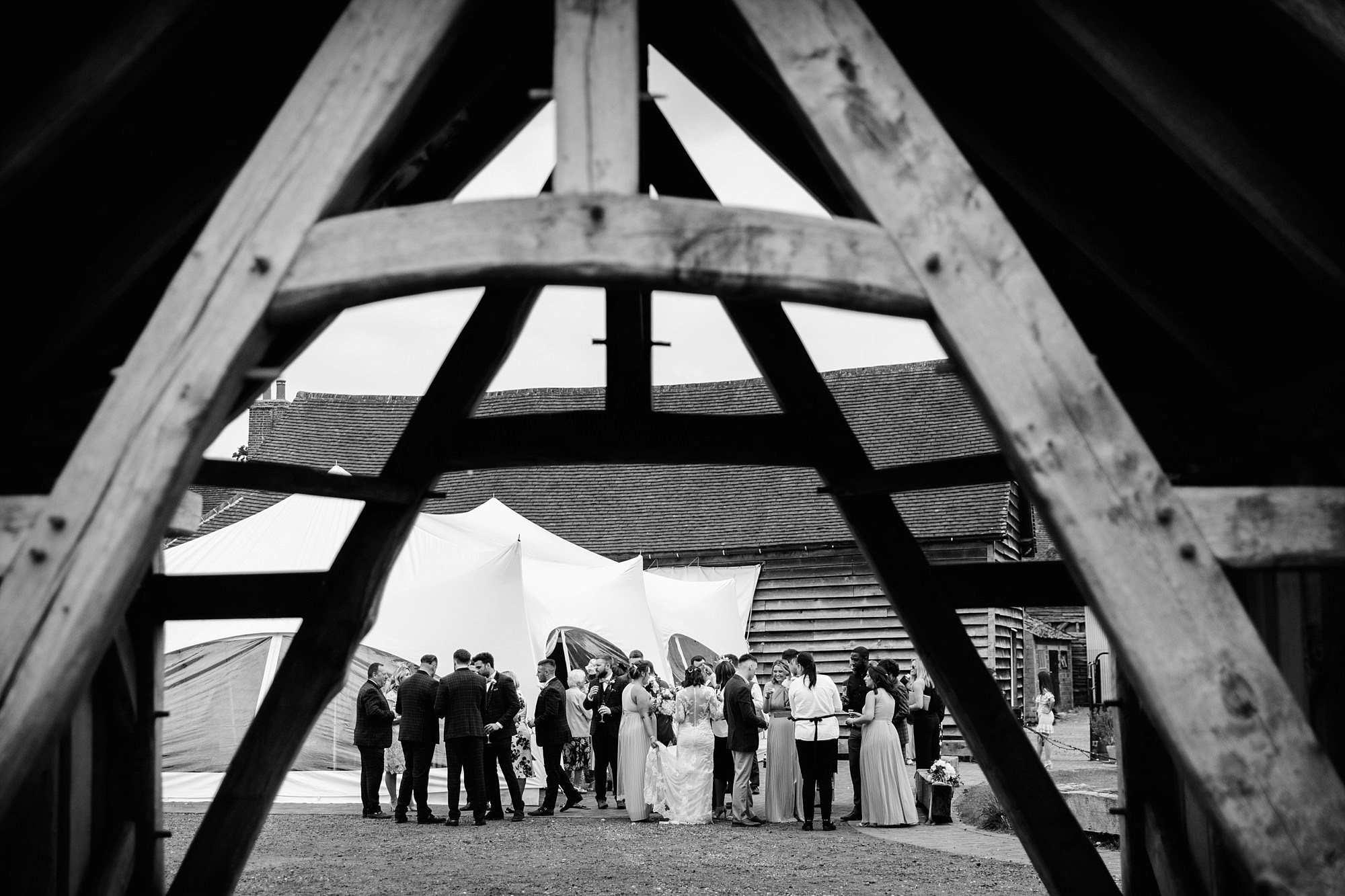 wedding guests chat together outside old greens barn