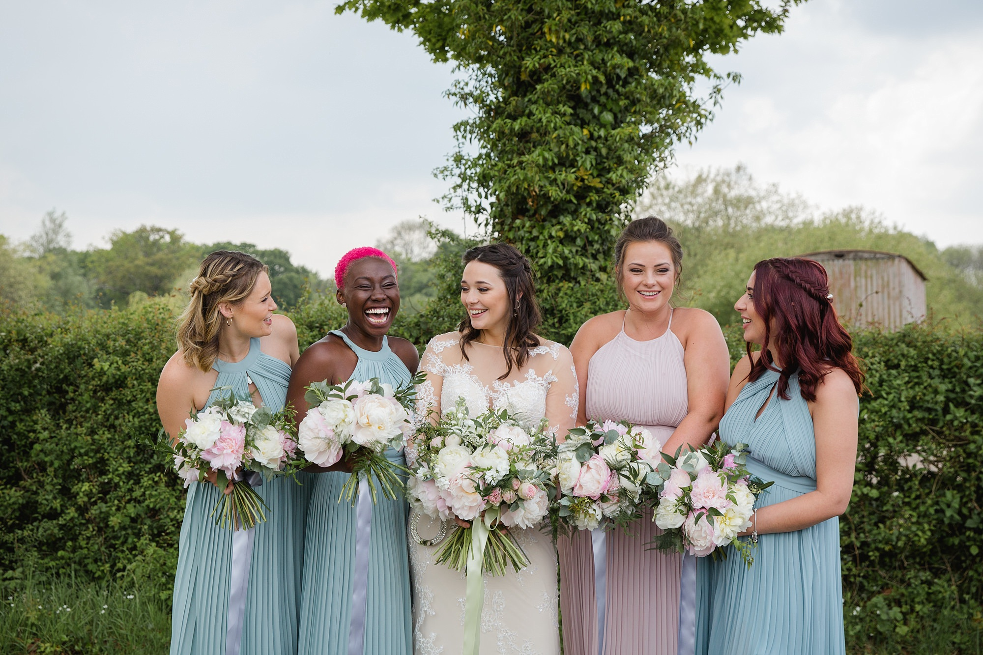 humanist wedding old greens barn bride and bridesmaids laugh together