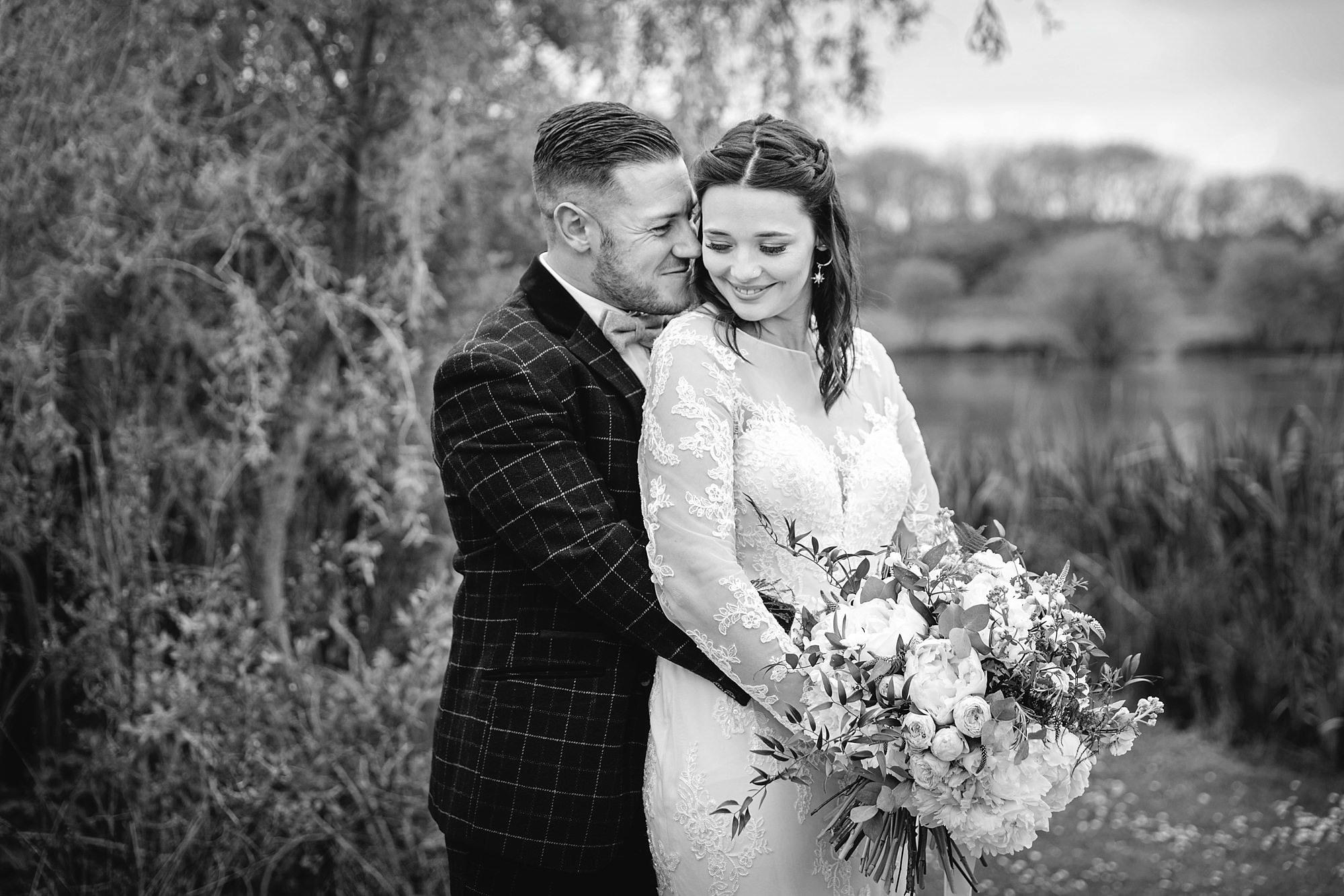 humanist wedding old greens barn groom hugging bride by lake