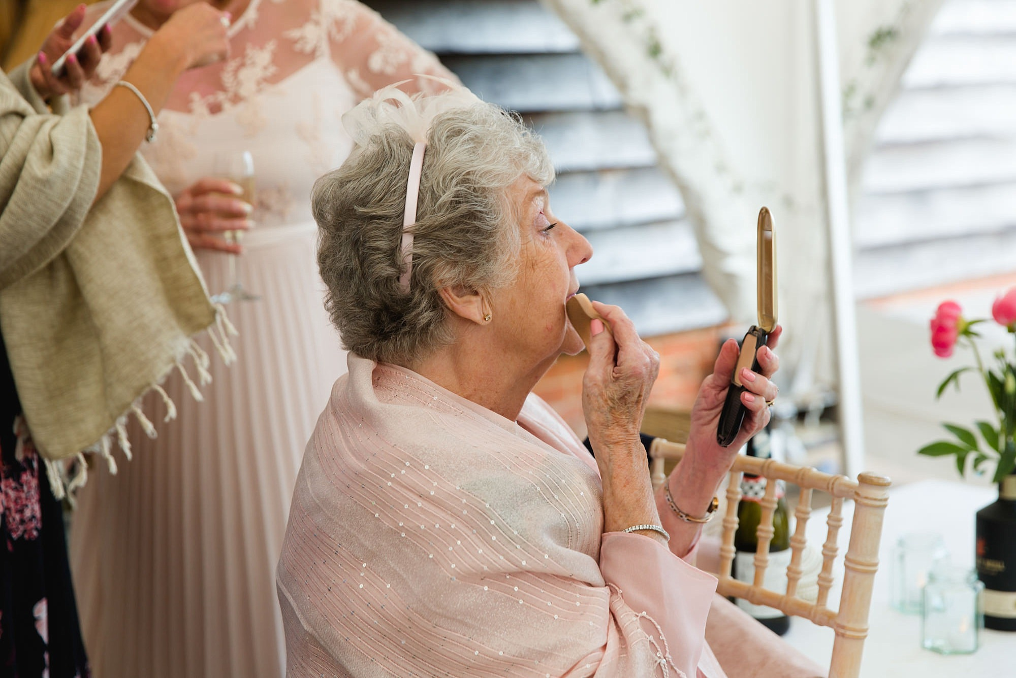 wedding guest reapplies makeup during reception at old greens barn wedding