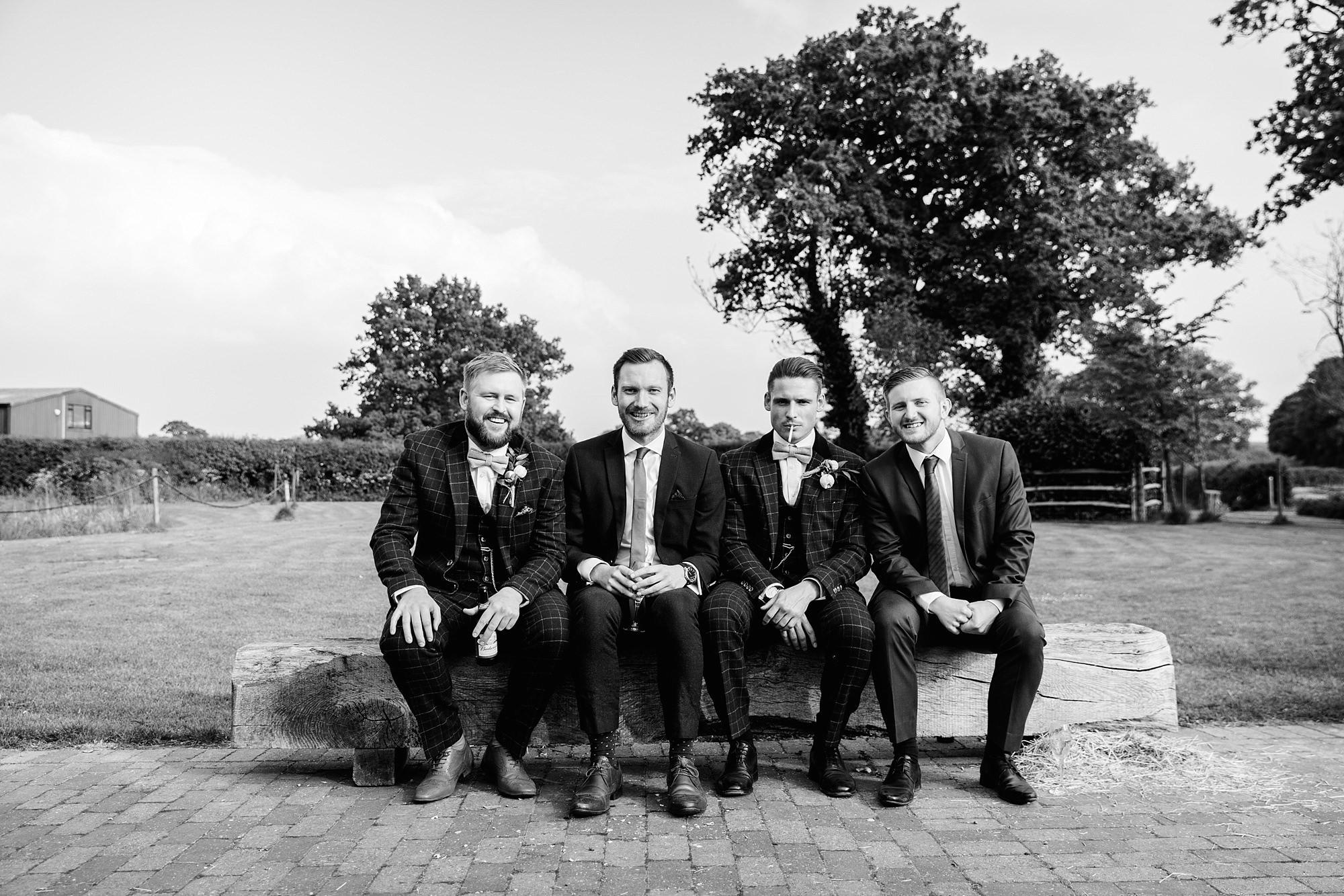 humanist wedding old greens barn groomsmen sit together