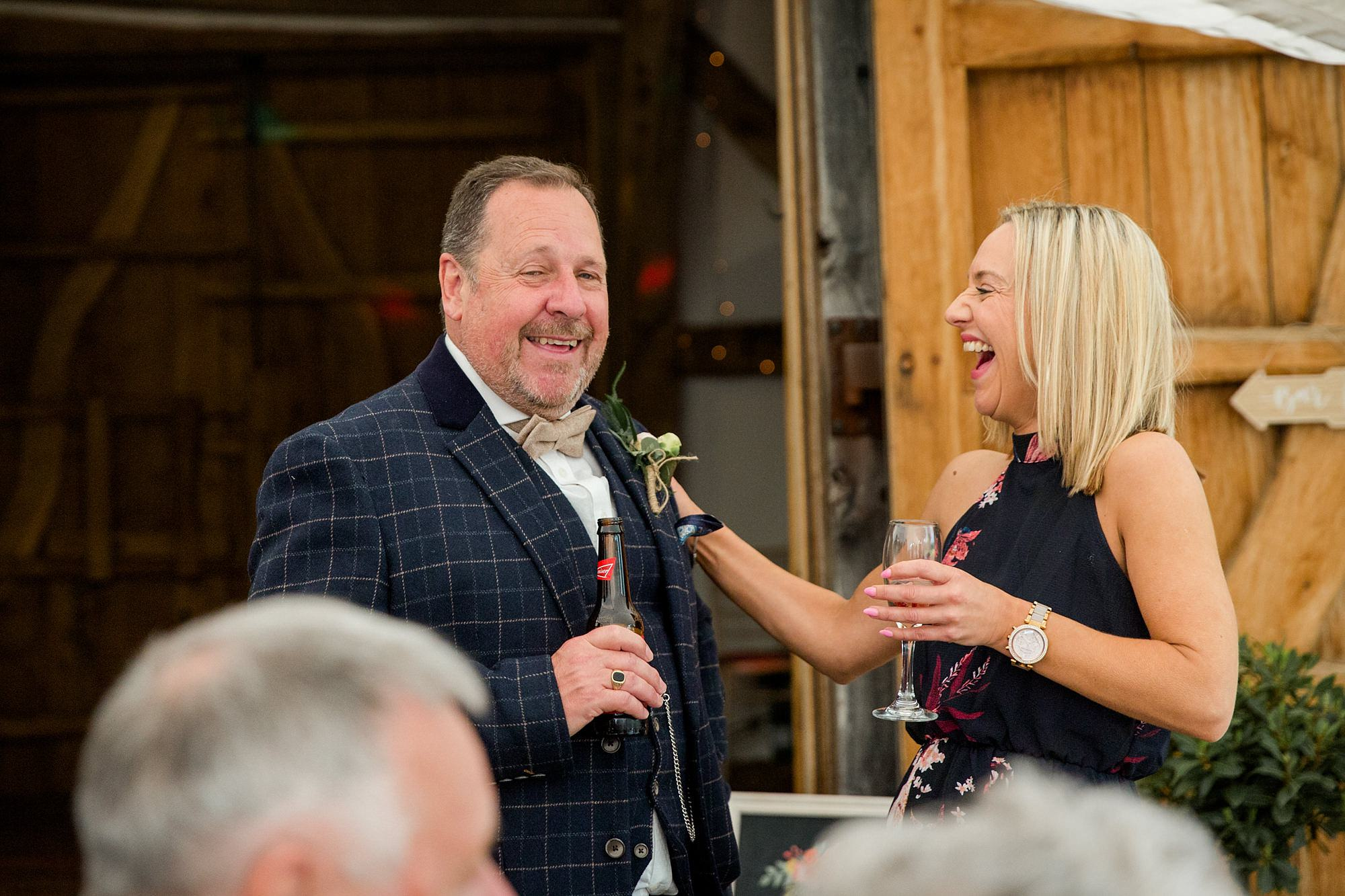 guests laugh together during reception at old greens barn humanist wedding