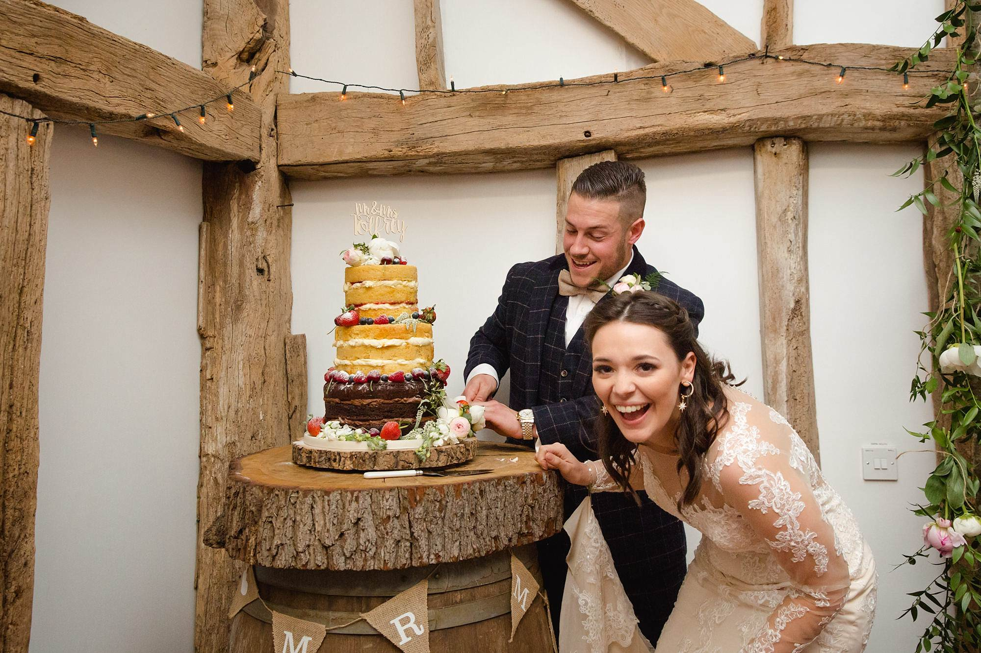 humanist wedding old greens barn bride and groom laugh and cut cake