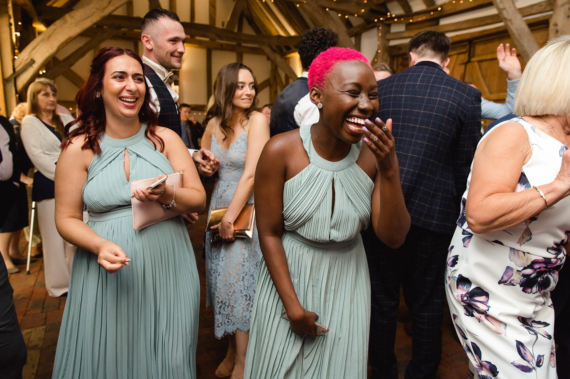 humanist wedding old greens barn bridesmaids laugh and dance together