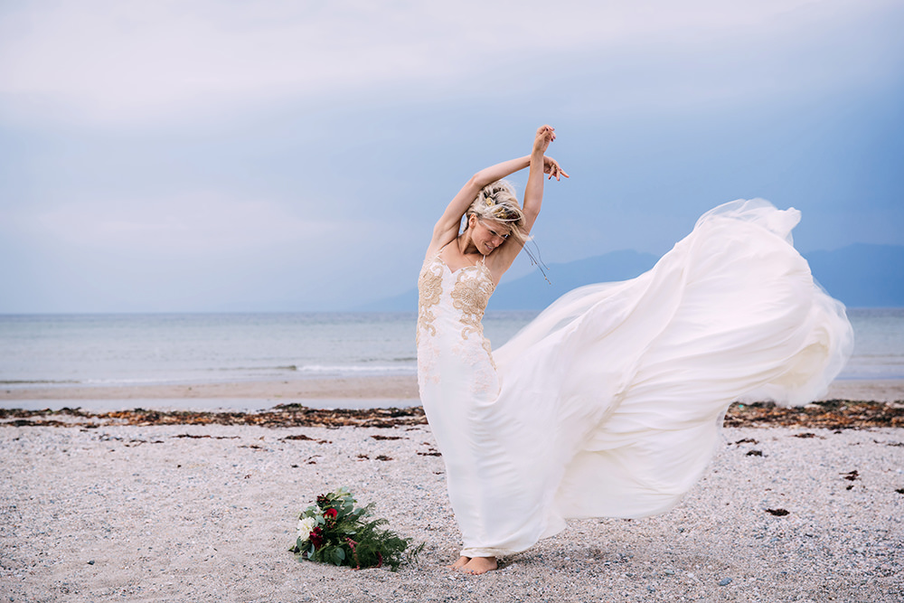 bride posing with flowing dress on windy scottish beach