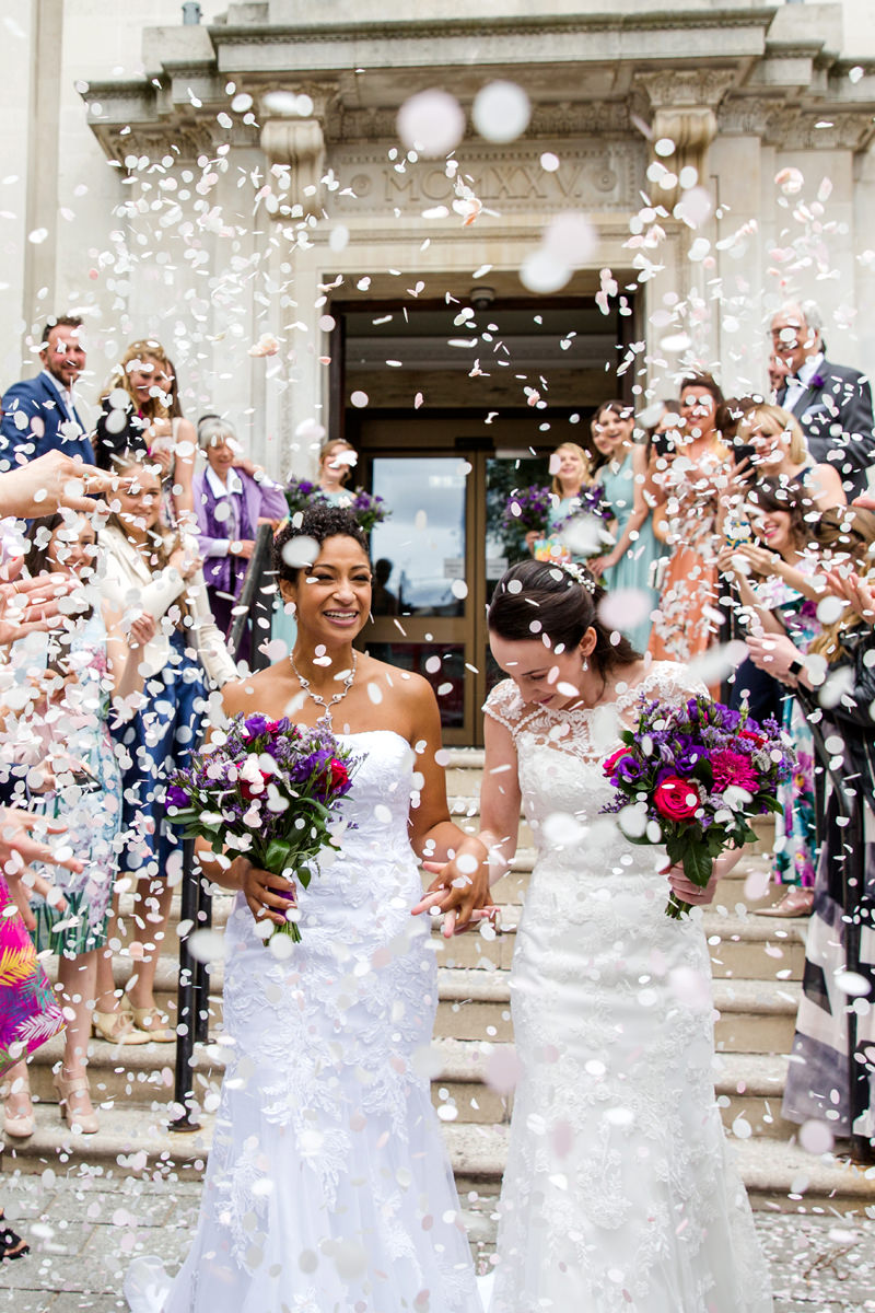 brides walking through white paper confetti in Islington