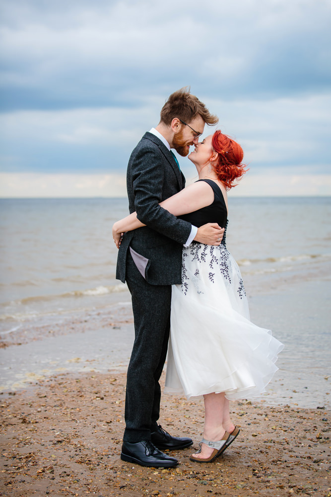 a bride and groom kiss on Whitstable beach