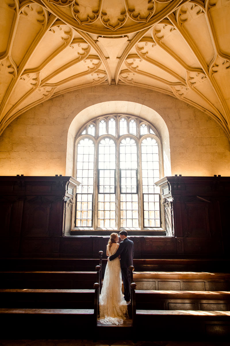 bride and groom in front of window at convocation house