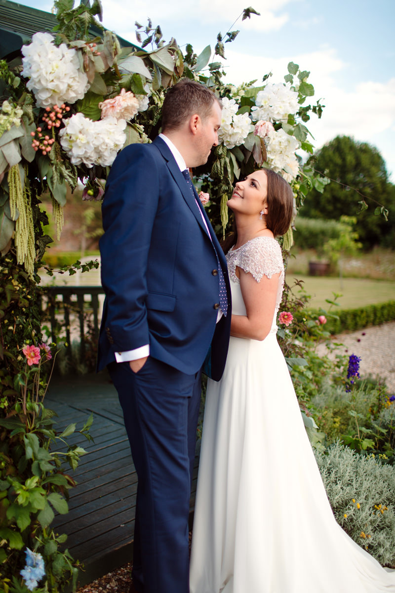 bride and groom with floral decorations at secret garden kent