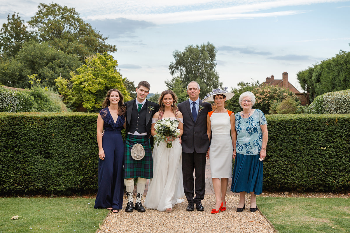 bride and groom with family in gardens
